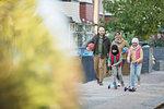 Muslim family walking and riding scooters on neighborhood sidewalk