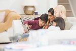 Family using digital tablet on living room sofa