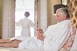 Mature man in spa bathrobe using digital tablet on hotel bed