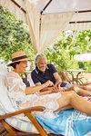 Mature couple using smart phone in cabana at resort poolside