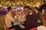 Portrait smiling man drinking wine, enjoying dinner garden party