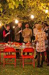 Friends talking under trees at dinner garden party