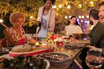 Friends enjoying candlelight dinner garden party