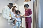 Female pediatrician examining girl patient in examination room