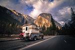 Campervan carrying touring motorcycle behind driving towards Yosemite National Park, California, USA