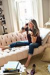 Stylish mature woman sitting on sofa making smartphone call