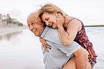 Couple playing piggyback ride on beach