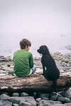 Boy and dog enjoying seaside