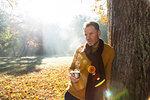 Man having warm drink against tree in park, Strandbad, Mannheim, Germany