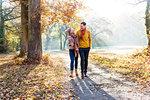 Couple walking in autumnal park, Strandbad, Mannheim, Germany