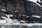 Tourists in dinghys near coastline, distant view, Burgerbukta, Spitsbergen, Svalbard, Norway.
