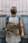 Axe maker wearing mask in workshop