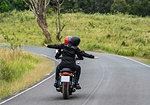 Couple riding motorbike on rural road at Khao Yai National park, rear view, Pak Chong, Nakhon Ratchasima, Thailand