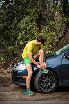 Runner tying shoelace beside car