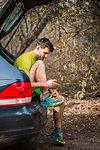 Runner tying shoelace in car trunk