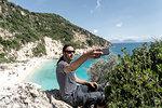 Man taking selfie on cliff top, Lefkada Island, Levkas, Greece