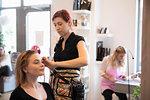 Female hairdresser drying customer's long hair in salon