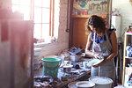Female potter checking glazed ceramic plate in workshop