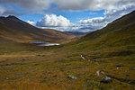 Male mountain biker biking on dirt track in mountain landscape, distant rear view,  Achnasheen, Scottish Highlands, Scotland