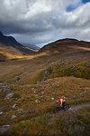 Male mountain biker biking on dirt track in mountain valley landscape, elevated view,  Achnasheen, Scottish Highlands, Scotland