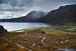 Male mountain biker biking on dirt track in mountain valley landscape, rear view,  Achnasheen, Scottish Highlands, Scotland