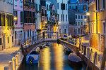 Moored boats and footbridge over Rio de la Toletta Canal,  old architectural style residential buildings at dusk, Dorsoduro district, Venice, Veneto, Italy