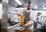 Chef serving pasta dish in Italian restaurant kitchen