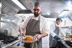 Chef presenting pasta dish in Italian restaurant kitchen