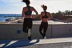 Friends jogging down steps in sports stadium