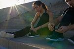 Friends tying shoelace on steps in sports stadium