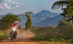 Biker riding scrambler type off road motorbike on dirt track, Nan, Thailand