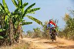 Biker riding scrambler type off road motorbike through banana plantation, Nan, Thailand