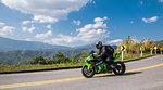 Biker riding motorbike on rural road, Nan, Thailand