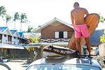 Man loading surfboards on top of vehicle, Pagudpud, Ilocos Norte, Philippines
