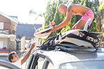Man helping friend load surfboards on top of vehicle, Pagudpud, Ilocos Norte, Philippines