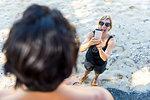 Woman taking photograph of friend on beach, Pagudpud, Ilocos Norte, Philippines