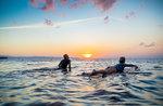 Surfers gliding in sea at sunset, Pagudpud, Ilocos Norte, Philippines