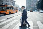 Senior businessman with wheeled luggage walking on pedestrian crossing, Milano, Lombardia, Italy
