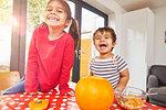 Children carving pumpkin in kitchen