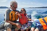 Grandfather and grandchildren on boat ride