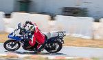 Male motorcyclist riding motorbike leaning sideways and speeding on race track,  Bangkok
