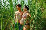 Pregnant couple in bikini and swim trunks standing in rural green corn field