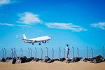 Boy on beach watching airplane flying low in blue sky near Lanzarote Airport, Spain