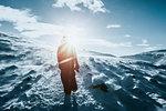 Man walking along sunny snow covered landscape, Reykjadalur, Iceland