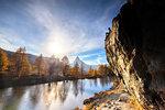 Man on rock above Grindjisee Lake during autumn in Zermatt, Switzerland, Europe