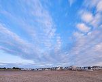 Sun illuminates houses and boats at Shelley Beach, Exmouth, Devon, England, United Kingdom, Europe