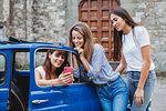 Friends using smartphone beside car