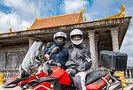 Bikers posing on ADV motorbike in front of buddhist temple, Phnom Penh, Cambodia