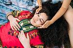 Young woman enjoying face massage by friend