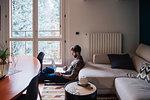 Mid adult man sitting on living room floor using laptop